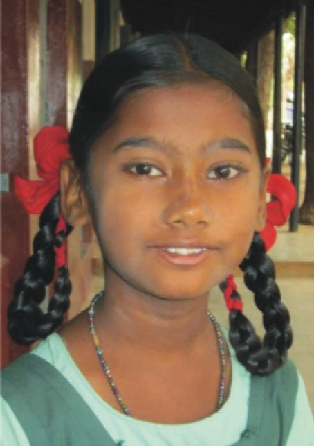 Head shot of Aathila Banu with pigtails in red ribbons