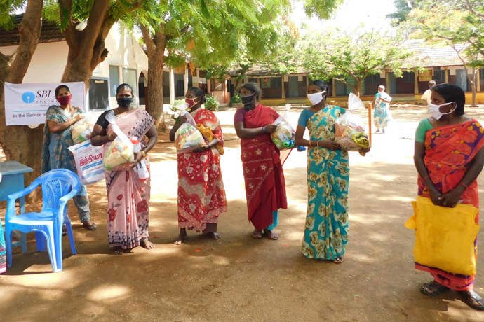 A group of local women holding the emergency dry ration packs they have been given at RTU