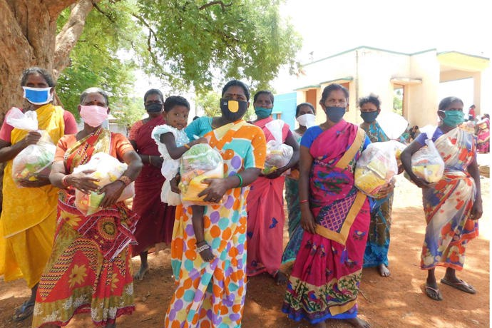 A group of women in colourful sarees receiving emergency dry good ration packs from RTU in India