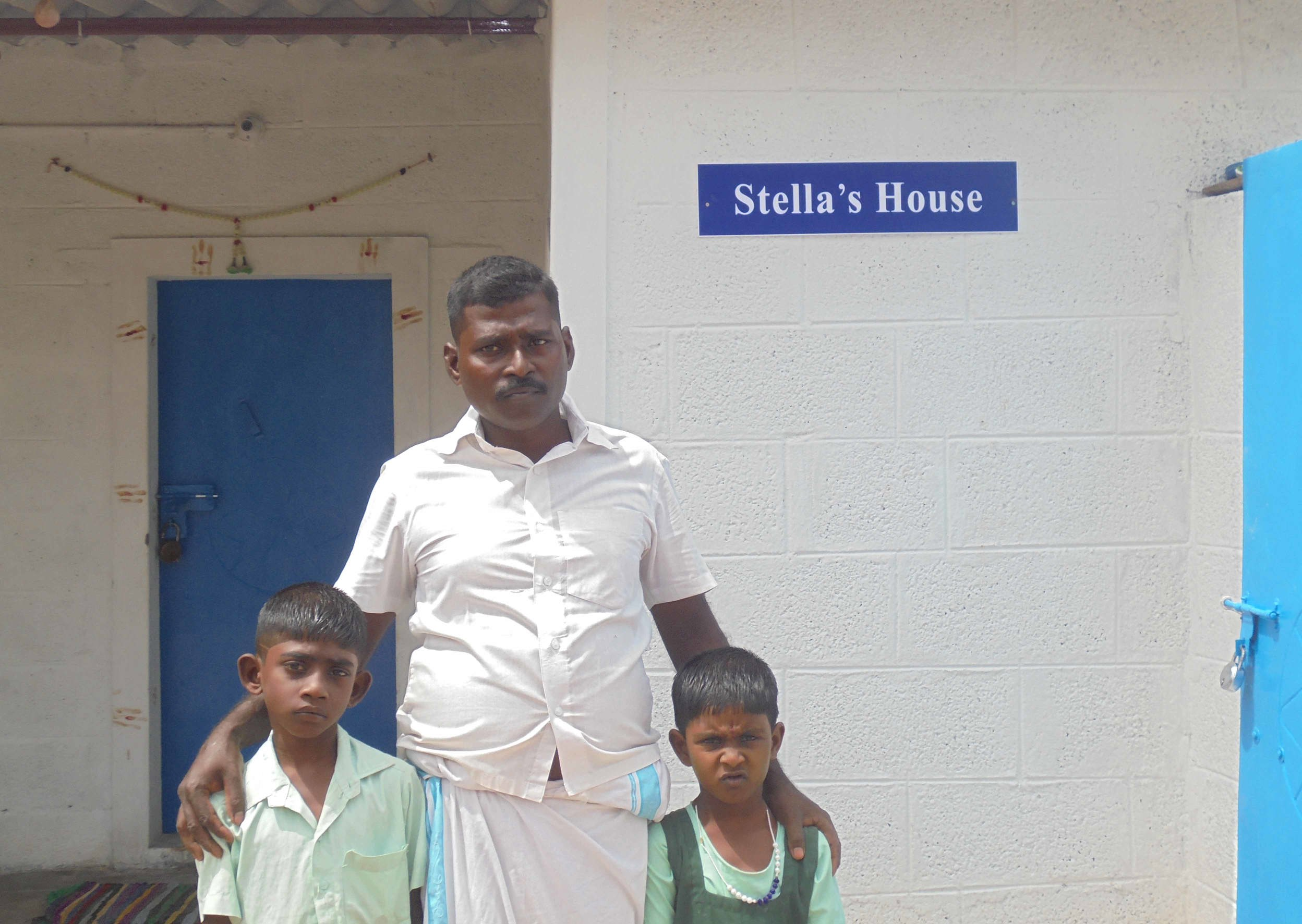 A father and his two children standing outside a house named Stella House