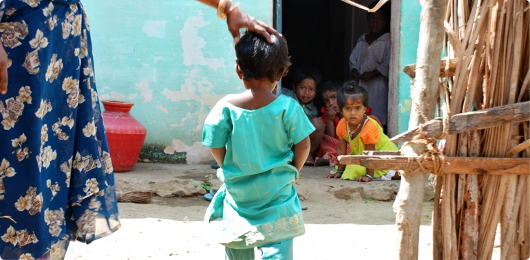A child walks away from the camera through the secure Childrens Village provided by Reaching the Unreached, a foster mothers hand on her head and other small children in a home in the background