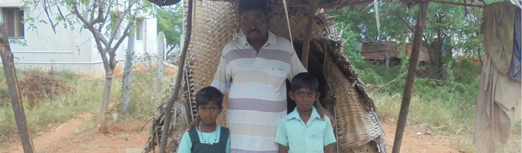A family in a rural village in South India outside their hut prior to having a house built for them by Reaching the Unreached