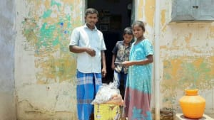 Rice and groceries being given to a HIV+ family outside their house
